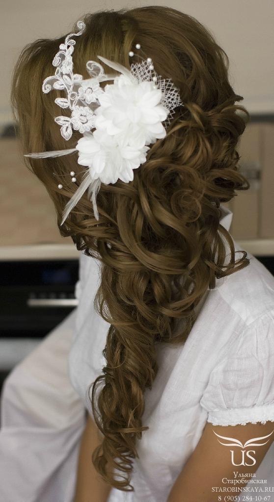 Модная свадебная прическа с собранными локонами на бок и красивой заколкой.