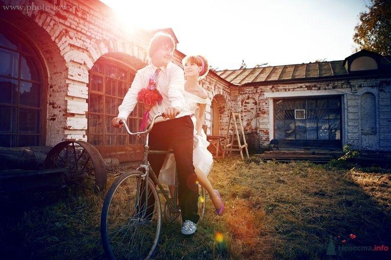Жених и невеста едут вместе на велосипеде возле старого дома