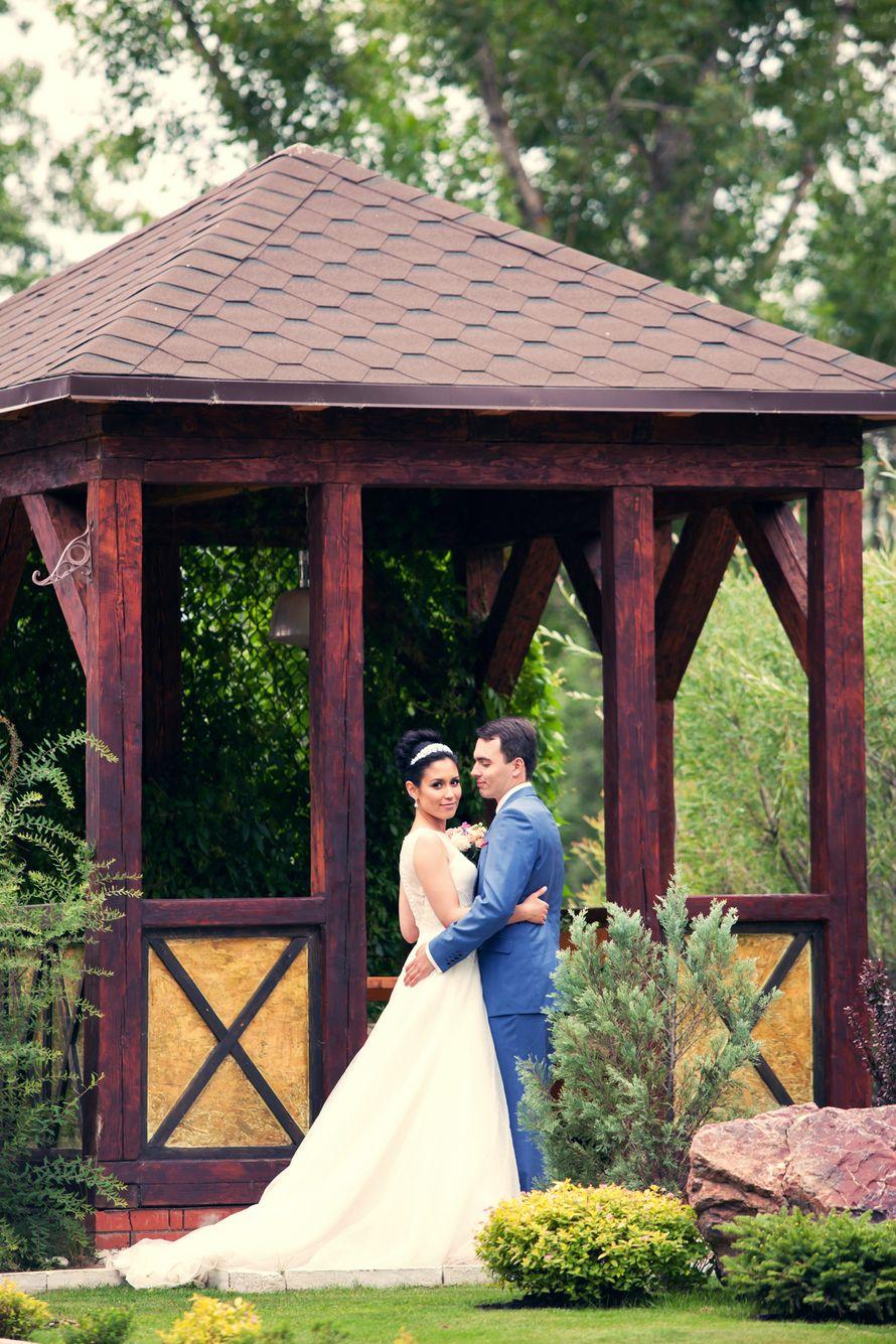 Жених и невеста, прислонившись друг к другу, стоят на фоне зелени возле беседки  - фото 3622659 Фотографы Виталий и Дарья Андриановы