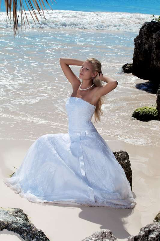 Невеста в белом кружевном открытом платье присела у камня на песочном пляже у самых волн - фото 575716 GoldMLB - свадьба в Доминикане