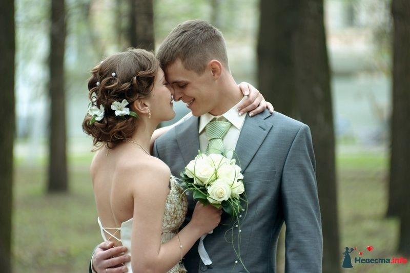 Жених и невеста стоят, прислонившись друг к другу, возле дерева в лесу