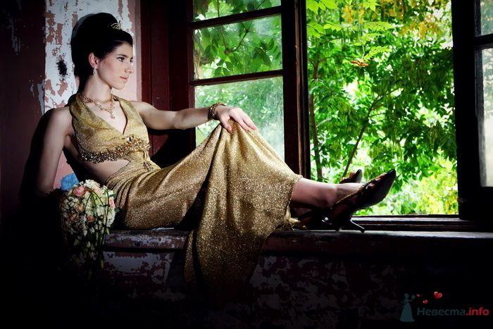 Невеста в длинном золотистом платье сидит у окна