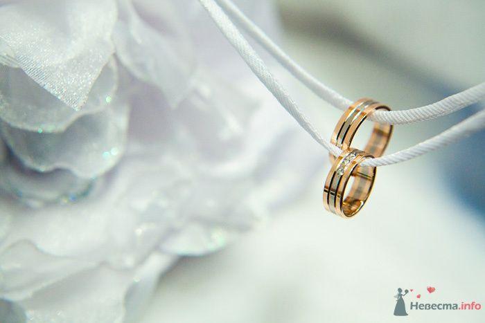 Обручальные кольца с белой лентой по центру на фоне шнуровки