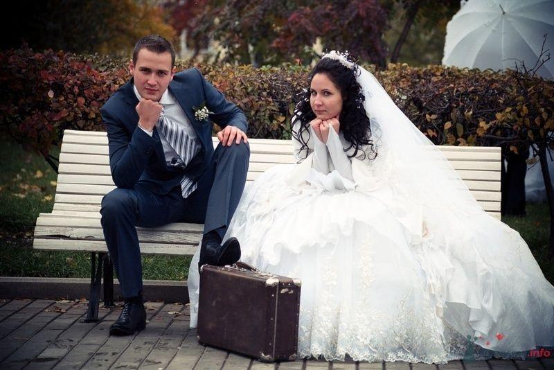 Жених и невеста сидят на белой скамейке в парке