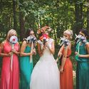 В лесу невеста в белом пышном платье с веночком из живых цветов и букетом и подружки в длинных открытых платьях розового, красного, бирюзового и оранжевого цветов, держат таблички