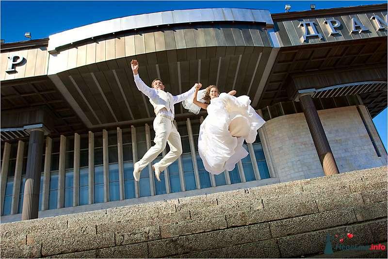 Жених и невеста, взявшись за руки,  подпрыгивают возле здания - фото 94173 Light Photo Studio - фотограф