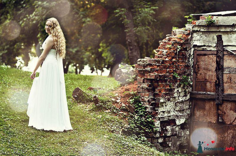 Невеста стоит в лесу возле старой кирпичной стены