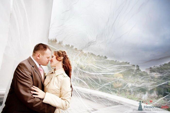 Жених и невеста, прислонившись друг к другу, стоят на панорамы города
