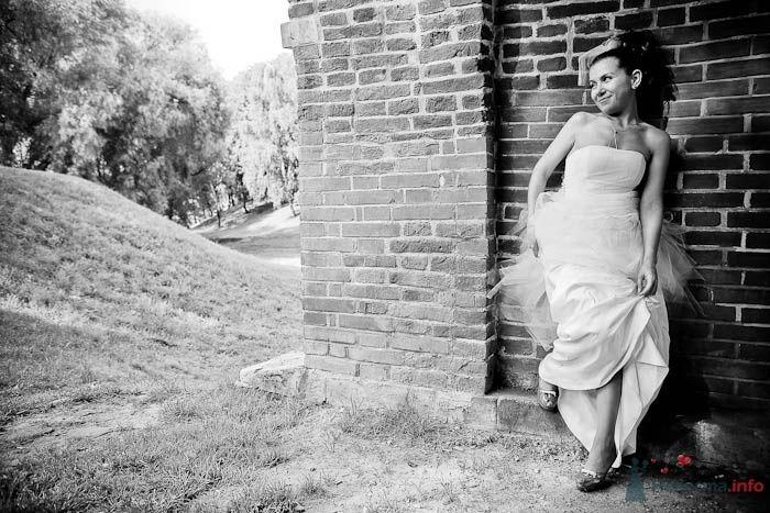 Невеста в белом длинном платье стоит возле кирпичной стены - фото 42019 Фотограф Елена Зотова