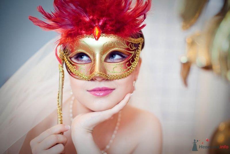 Невеста прикрывает лицо золотой венецианской маской на ручке, декорированной тесьмой и красными перьями - фото 68667 Фотограф Елена Зотова