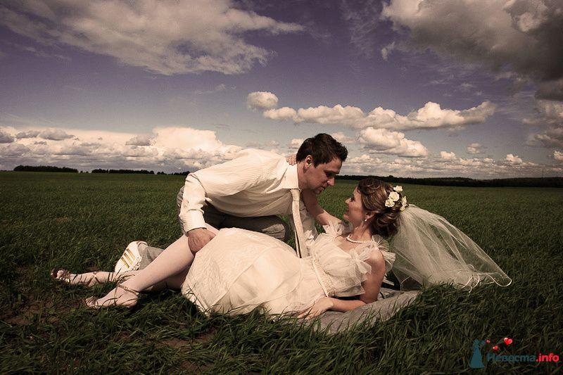 Жених и невеста лежат, прислонившись друг к другу, на траве в поле - фото 90902 LevBodrov