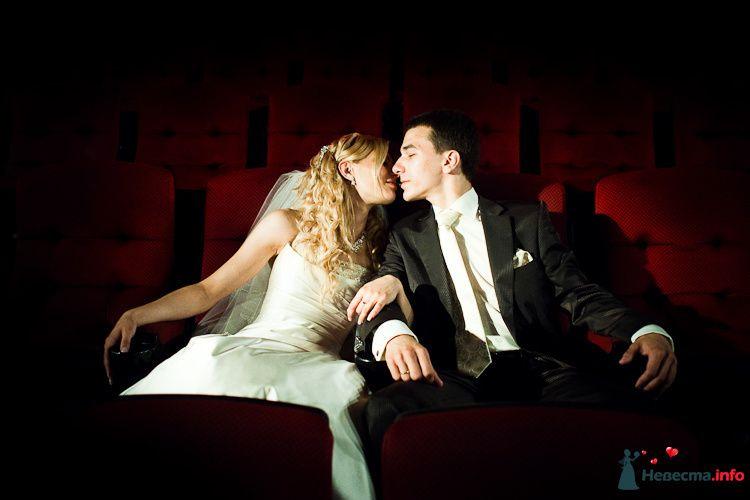 Жених и невеста сидят рядом на красных стульях в зале - фото 90920 LevBodrov
