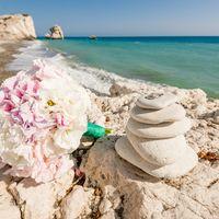 Букет невесты из белых эустом и розовых гортензий, декорированный ярко-зеленой лентой на каменном берегу моря