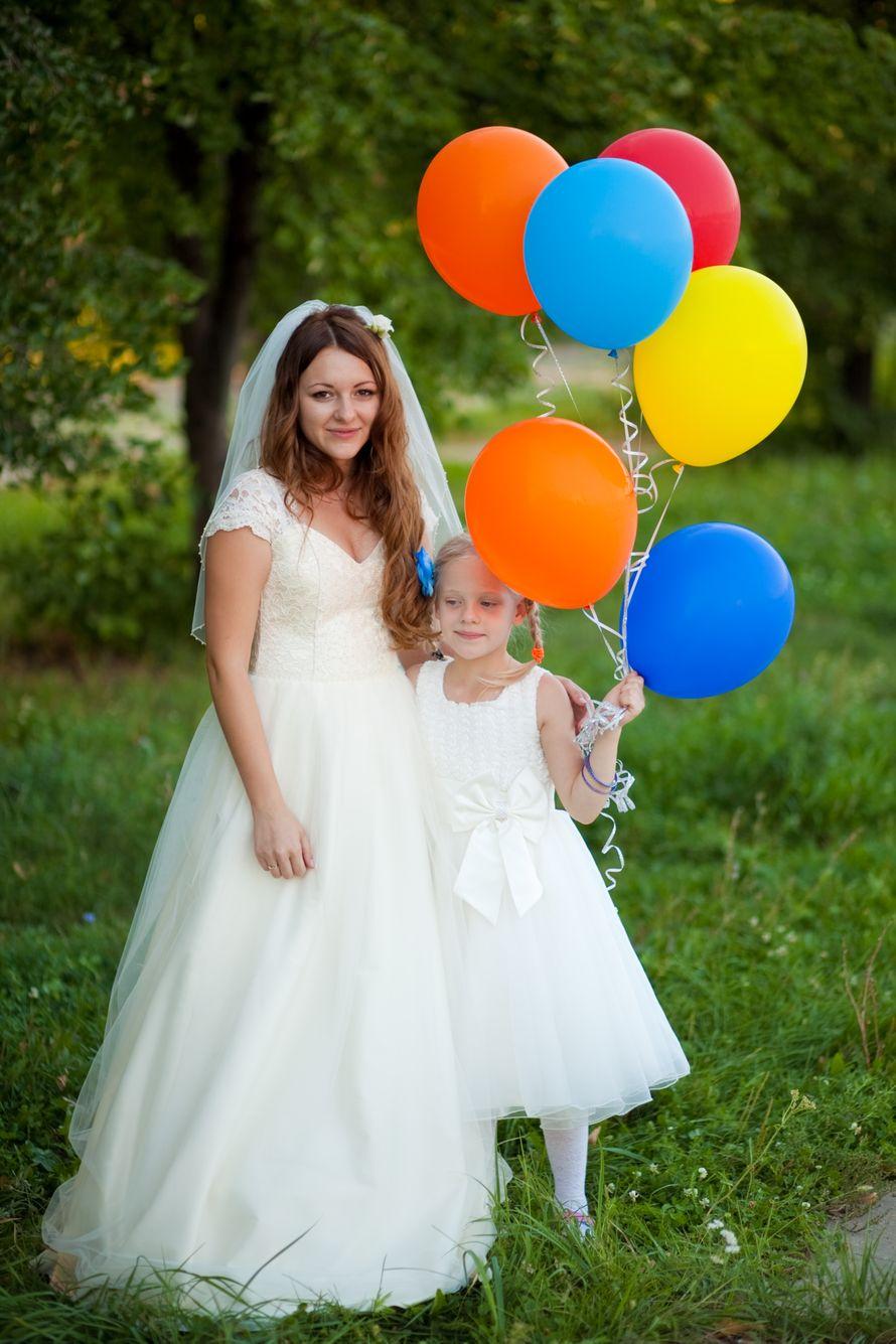 Девочка держит яркие воздушные шарики, рядом с невестой, на красивой  зеленой поляне в белом пышном длинном платье - фото 1774119 Пошив и ремонт вечерних платьев