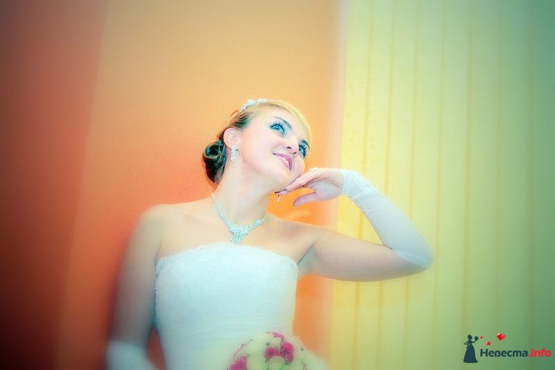 Невеста в белом платье с букетом цветов стоит на фоне оранжевой стены - фото 98500 Невеста01