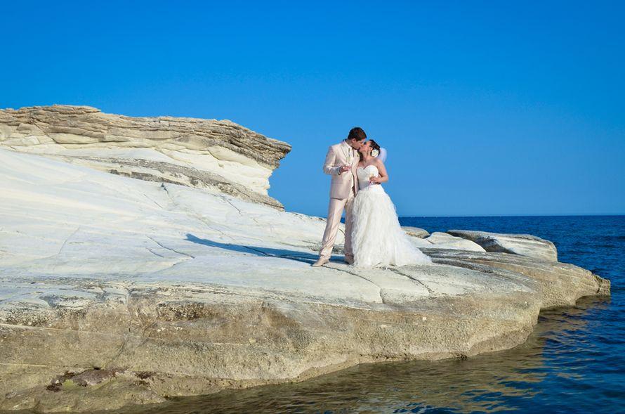 Молодожены в белых нарядах целуются на краю белой скалы уходящей в море - фото 905361 Агентство Гименей - организация свадеб на Кипре