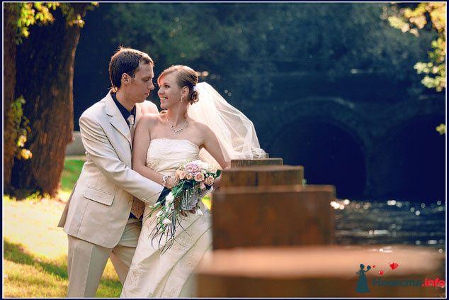 Жених и невеста, прислонившись друг к другу, стоят на фоне зелени и