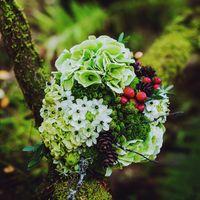 Букет лесной невесты из белого орнитогалума, зелено-белых гортензий, мха, хвороста, шишек и красных ягод гиперикума