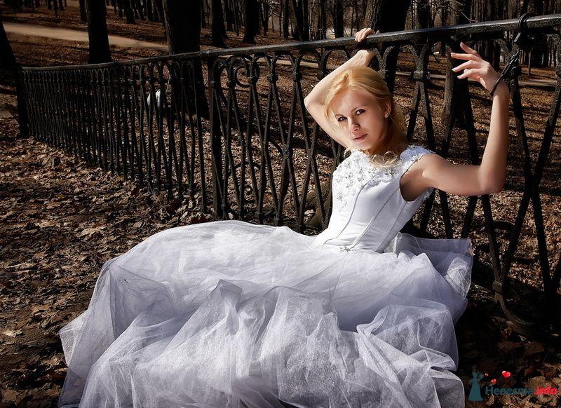 Невеста в белом длинном платье сидит в парке возле ограждения
