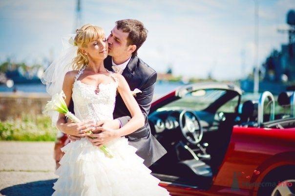 Жених и невеста стоят, прислонившись друг к другу, возле красной