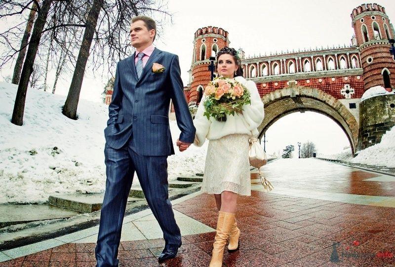 Жених и невеста, прислонившись друг к другу, стоят на фоне моста