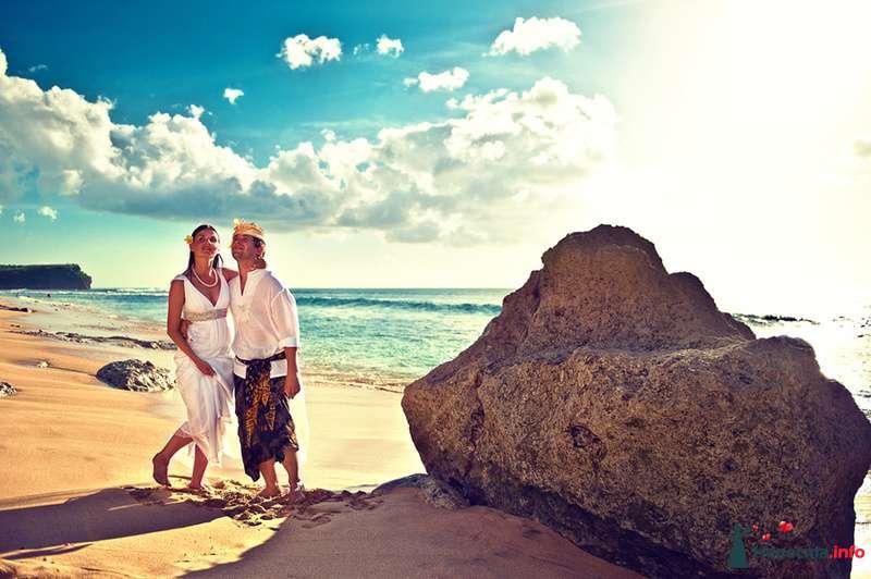 Молодожены стоят босиком на песке обнявшись возле огромного камня, она в белом платье. а жених в белой рубашке и полотенце - фото 115299 Ваш фотограф на Бали - Максим Коробейников