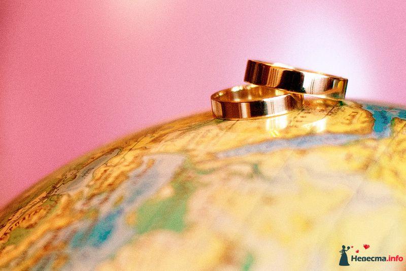 Золотые обручальные кольца, выполненные в классическом стиле, на фоне глобуса. - фото 121076 Невеста01