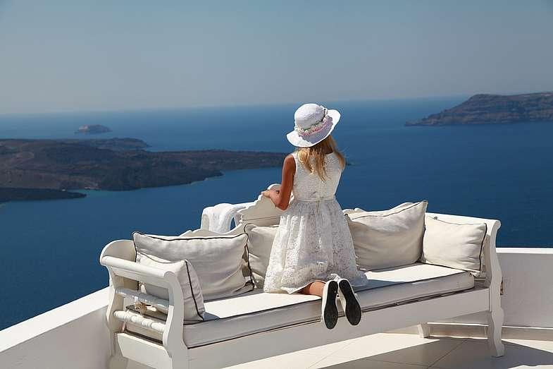 Девочка на диване в белом красивом платье с белой шляпкой смотрит на  бесконечные голубые воды  моря - фото 1338765 Exclusivaweddings - организация свадьбы на Санторини