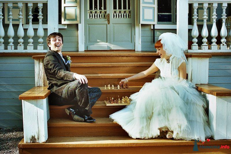 Жених и невеста сидят на деревянных ступеньках и играют в шахматы