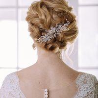 Свадебная прическа с плетением, украшенная легкой веточкой