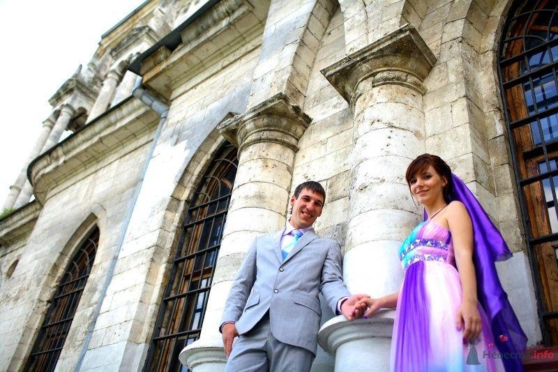 Жених и невеста, взявшись за руки, стоят на фоне здания