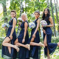 Подружки невесты в одинаковых длинных синих платьях приталенных на поясом с высоким разрезом в бежевой обуви и букетами из белых и голубых цветов в лесу