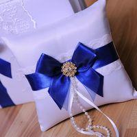 Подушечка для колец с темно-синей лентой и золотым украшением на банте