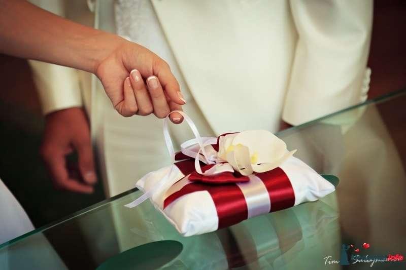 Белая атласная подушечка для колец украшена красной и белой атласными лентами, бантом и цветком орхидеи - фото 398458 Айрушик