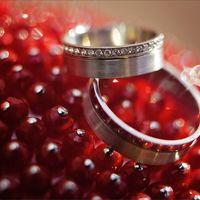 Обручальные кольца на фоне россыпи красных бусин.