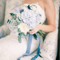 Невеста в белом кружевном платье с букетом невесты из голубых гортензий и белых роз, завязанный синей лентой, в белом мягком кресле с голубым голландским узором