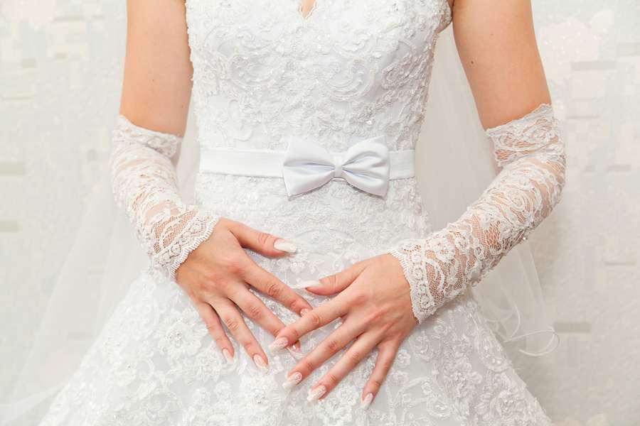 Руки невесты на фоне свадебного платья, маникюр - перламутровый лак. - фото 1779221 Фотограф Ерошин Тарас