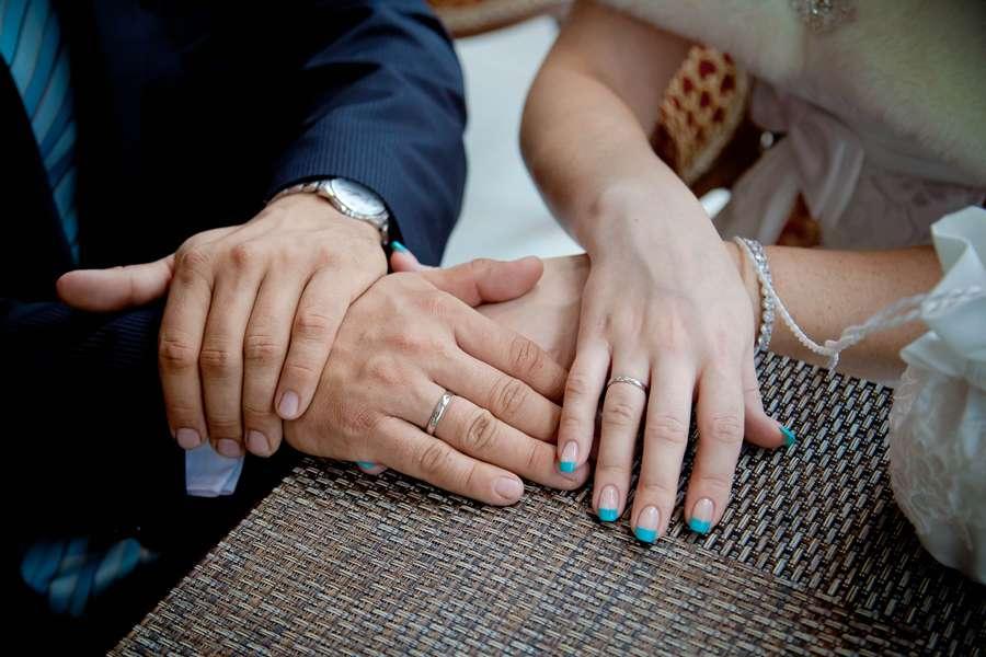Руки невесты на фоне рук жениха и серой столешницы, маникюр - бирюзовый френч. - фото 1779387 Фотограф Ерошин Тарас