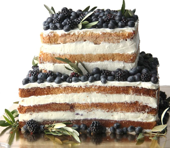 Торт с фруктами и цветами на свадьбу на фото выглядит отлично: с сиреневыми плодами.