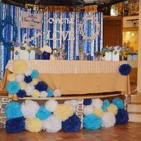Сцена, на которой распологался стол молодоженов декорирована пумпонами различных размеров в палитре концепции свадьбы!