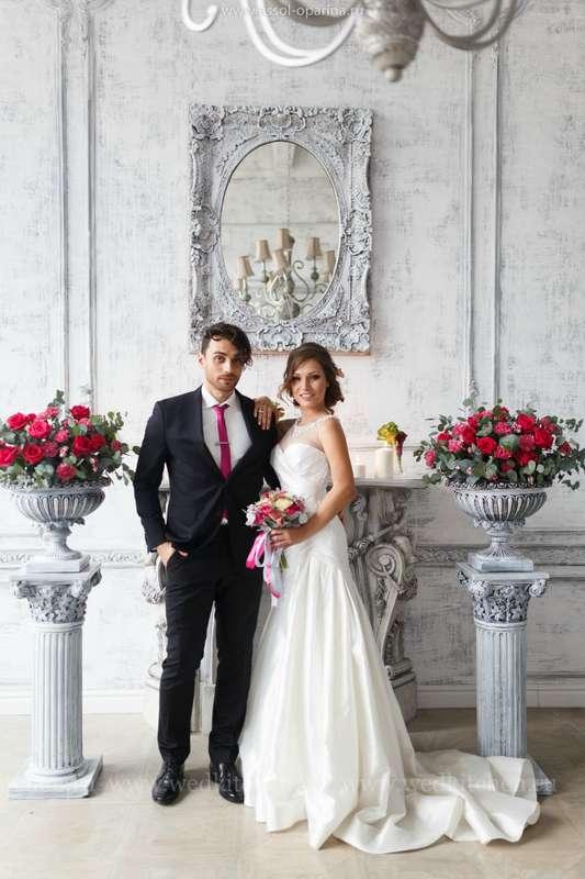 """Жених и невеста, прислонившись друг к другу, стоят в комнате у камина и горшков с красными цветами - фото 3472915 Свадебное агентство """"Wedkitchen"""""""