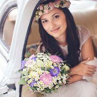 Невеста в венке из роз и ромашек с букетом невесты в руках