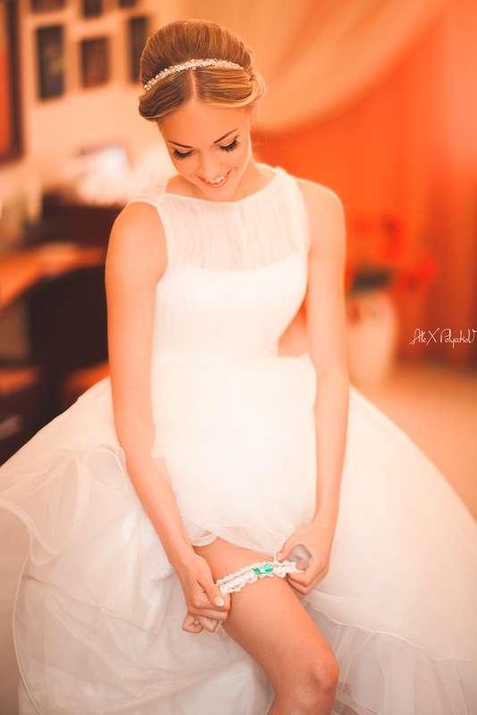 Невеста одевает на ногу белую кружевную подвязку с голубым атласным бантом - фото 2513189 Свадебный Фотограф Александр Поляков