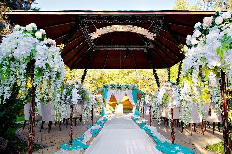 Квадратная арка с композицией из живых цветов, задрапированная бело- голубой тканью, на фоне стульев для гостей в цветах - фото 2214314 Бюро Амурных Дел - выездная регистрация брака