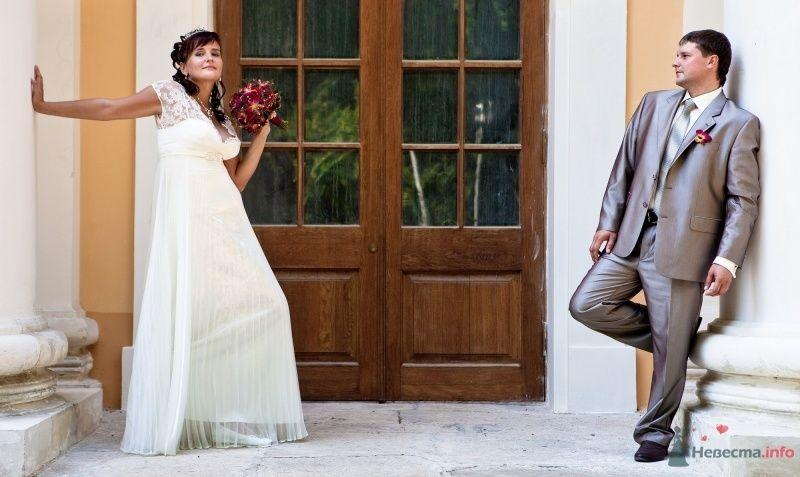 Жених и невеста стоят вместе у входа в дом