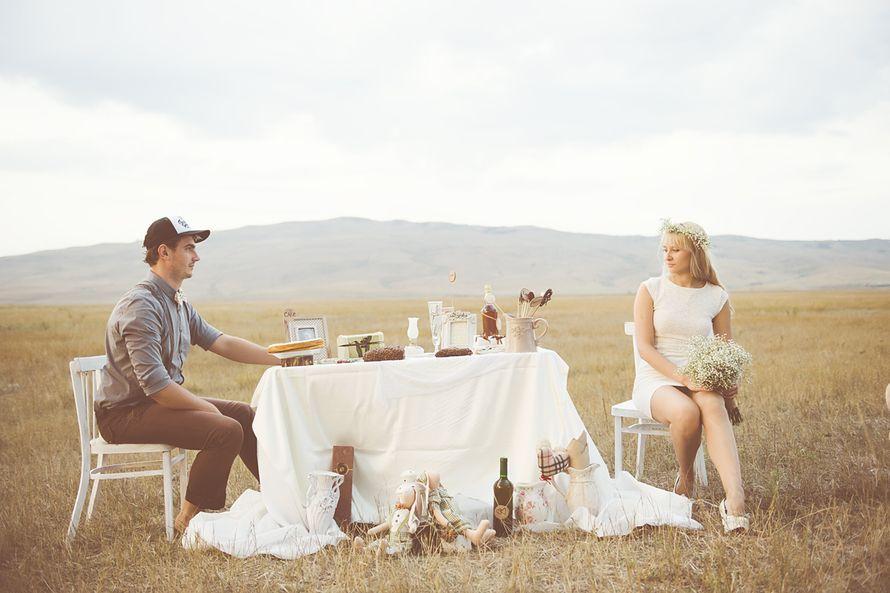 Жених и невеста сидят посреди поля за маленьким столиком, украшенным белой скатертью - фото 1596501 Фотограф Манвелов Николай