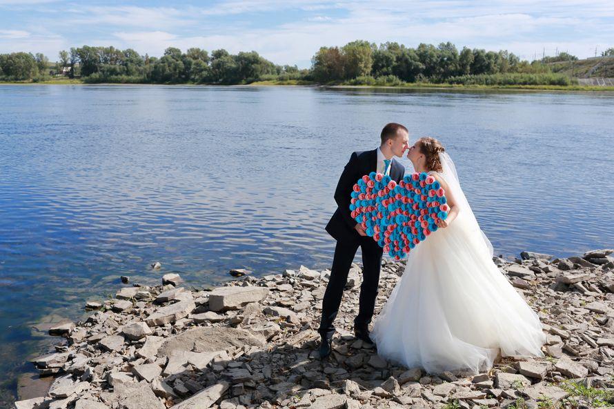 На фоне реки, целуются жених и невеста, держа в руках розово-голубое сердце - фото 3031095 Фотограф Анна Беховская