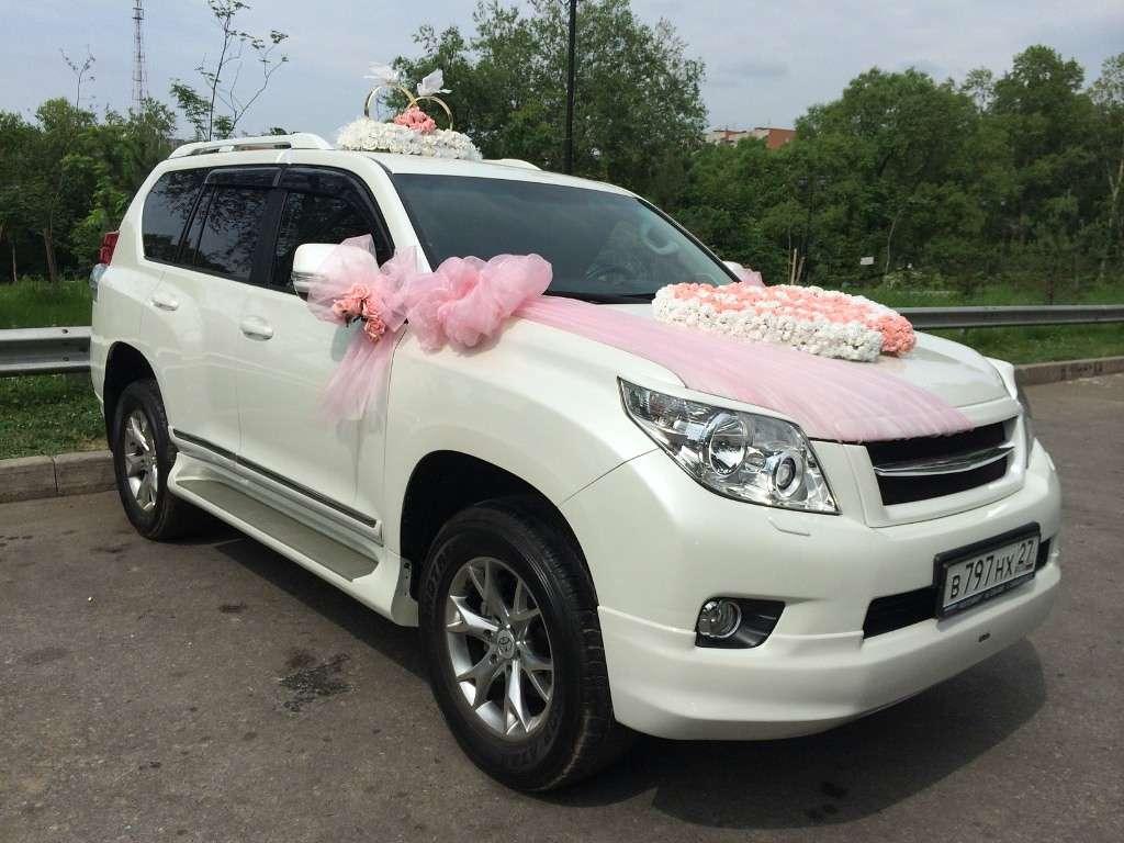 Белый шикарный автомобиль, украшенный розовым фатином и экибаной в виде двойного розово - белого сердца, на крыше стойка из - фото 2681655 Сэланджи Студио - букеты, оформление авто