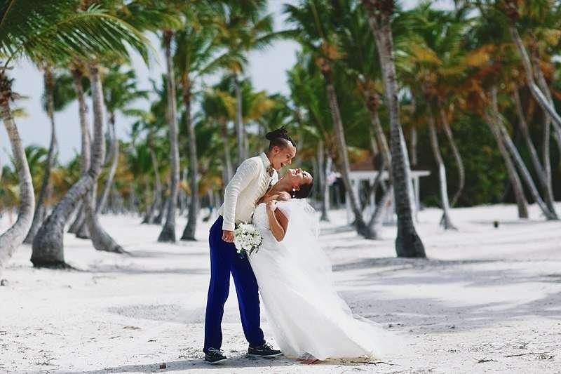 Среди тропических деревьев веселятся молодожены, жених в синих брюках и белой рубашке наклонил невесту в белом платье назад, - фото 2818093 Destiny dress - show room, свадебные платья