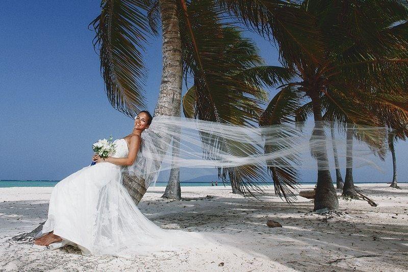 На тропическом пляже невеста в белоснежном пышном платье с корсетом и длинной фатой лежит на стволе пальмы, в руках она держит - фото 2818097 Destiny dress - show room, свадебные платья